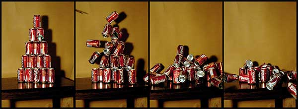 Image sequence of a tower of coke cans being hit by a shot from the Super Maul